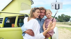 Family standing in front of camper van taking selfie picture Stock Footage