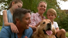 Happy family in the park with their dog - stock footage