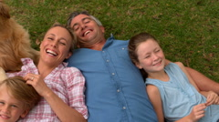 Happy family smiling at the camera with their dog - stock footage