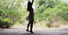 Silhouette of Young healthy Asian woman dancing at the park Stock Footage