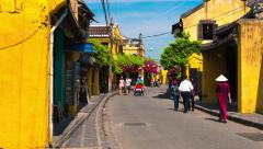 Hoi An - May 2015: Ancient city street view with people and bicycles. 4K Stock Footage