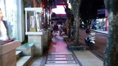 Shop barker drum, night street, tourist pass by, camera approach and turn around Stock Footage
