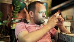 Young man playing game on smartphone sitting in cafe  HD Stock Footage