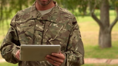 Stock Video Footage of Soldier looking at tablet pc in park