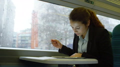 4k, young businesswoman planning for meeting on early morning commuter train - stock footage