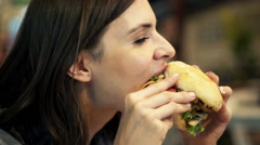 Stock Video Footage of Young woman eating fast food, hamburger in cafe HD