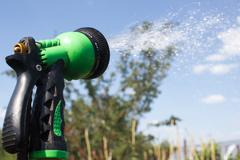 Watering lawn grass with a shower sprayer head Stock Photos