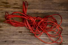 Red Rope and Textured Wood, Coil of ???? set against highly textured wood. - stock photo