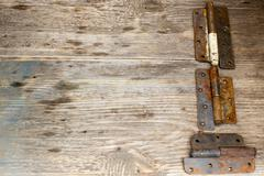 Metal door hinge on a grungy wooden background,  Copy space to right. Stock Photos