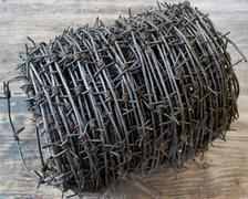 Roll of barbed Wire, on a wooden background - stock photo
