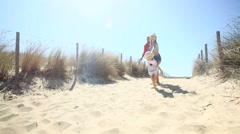 Family running on the sand dune to the beach Stock Footage