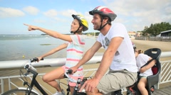 Couple with kid riding bicycle on a pontoon - stock footage