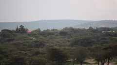 Houses on hill in poor town of Maralal, Samburu, Kenya, Africa, pan right Stock Footage