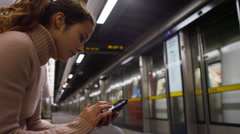 4k Young woman using smartphone on busy subway train station at night Stock Footage