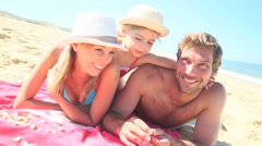 Portrait of family laying on the beach in summer Stock Footage