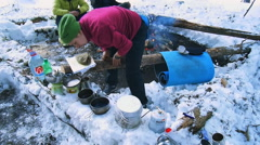 Tourists on a halt heated, dried clothes and prepare food a campfire Stock Footage