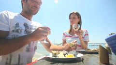 Couple at seafood outdoors restaurant tasting fresh oysters - stock footage