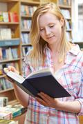 Young Woman Reading Book In Bookstore Stock Photos