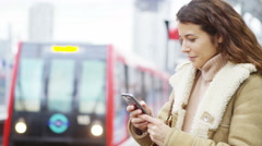 4k Young, attractive woman texting on smartphone as train comes into station Stock Footage