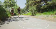 Young women playing hop-scotch at a park Stock Footage