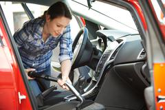 Woman Cleaning Interior Of Car Using Vacuum Cleaner - stock photo