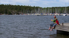 A father and his son sitting on a jetty fishing, Sweden. - stock footage