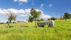 An old fertilizer trailer on a green meadow with a village in the background  - stock photo