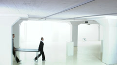 Man and woman carrying a table in a white and empty office premises, Sweden. Stock Footage