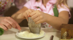 Daughter grating cheese, mother tasting it, Stockholm, Sweden. - stock footage