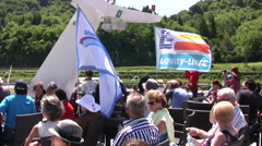 Passengers sitting on the top deck of a cruise boat on the Rhine river Stock Footage
