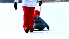 Grown-up pulling a little sledge with a child in, Sweden. Stock Footage