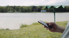 Pregnant woman using mobile phone in park Stock Footage