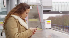 4k young attractive female texting on smartphone whilst waiting at train station Stock Footage