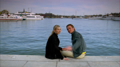 Scandinavian couple sitting by the sea, Sweden. - stock footage