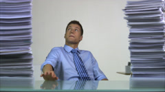 A business man sitting behind a desk, piles of paper decreasing, Sweden. - stock footage