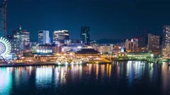 Panning time lapse of ships entering colorful Kobe harbor at night.  Stock Footage