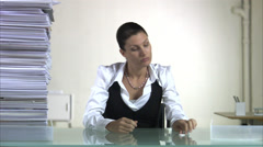 A woman sitting in an office polishing her nails when a pile of paper next to Stock Footage