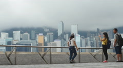 Girl walks through HK harbor holding sefie stick 4K Stock Footage