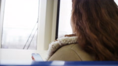 4k Cheerful, young female texting on smartphone on moving train Stock Footage