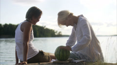 Two young women cutting a watermelon, Blido, Stockholm archipelago, Sweden. Stock Footage