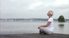 A woman sitting on a jetty, Sweden. - stock footage