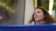 4k young female smiling and looking out the window of a subway train Stock Footage