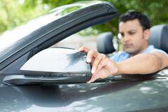 Closeup portrait, young man driver looking adjusting side view car mirror, ma - stock photo