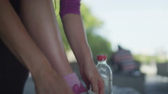 Female jogger tying up her shoe lace before a run in slow motion Stock Footage