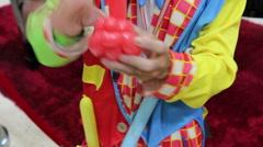 Joker making fancy ballon doll for children - stock footage