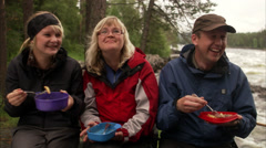 People eating sitting around a camp fire, Sweden. Stock Footage