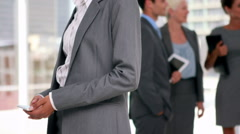 Businesswoman having a phone call with colleague in background Stock Footage
