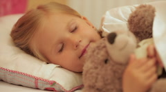 Cute little girl sleeping with her teddy bear Stock Footage