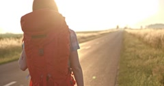 Traveler woman hitchhiking on a sunny road and walking. Young happy backpacker - stock footage