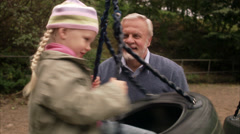 An elderly man with granddaughter in a playground, Sweden. Stock Footage
